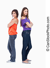 Teenage girls wearing casual clothes while standing back to back