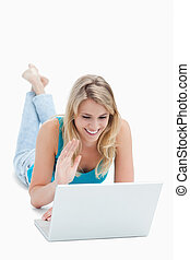 A woman with a laptop has her hand up and is lying on the floor against a white background