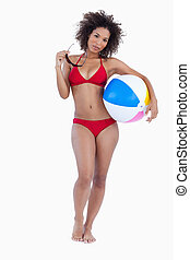 Attractive woman holding her sunglasses and a beach ball