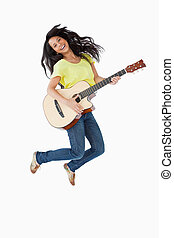 Young Latino woman holding a guitar while jumping
