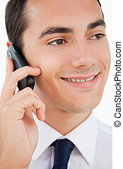 Close-up of a smiling man in a suit using his cellphone