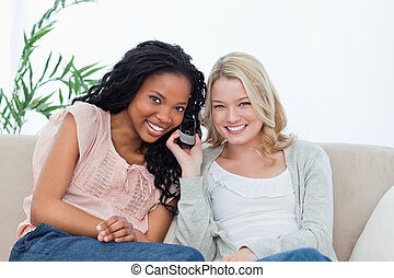 Two women listening to a mobile phone are smiling at the camera