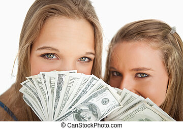 Close-up of two young woman behind dollars against white...