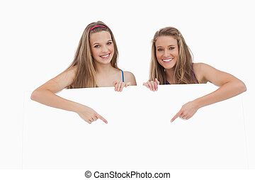 Portrait of young women holding and pointing a blank sign...