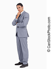 Thoughtful businessman smiling with folded arms