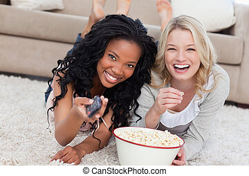 Two women lying on the ground with popcorn are smiling at...