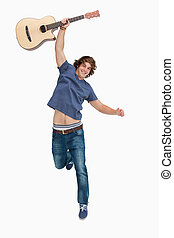 Male student jumping with his guitar