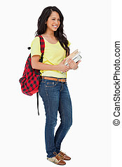 Smiling Latin student with backpack holding textbooks...
