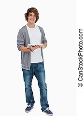 Male student posing while holding a touch pad against white...