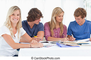 A study group working hard as one girl smiles and looks at the camera with her hands on the table