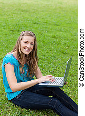 Young beautiful girl looking at the camera while using her laptop in the countryside