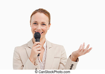Pretty woman in a suit speaking with a microphone against...