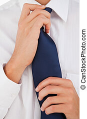 Man tightening his tie - Close-up of a man tightening his...