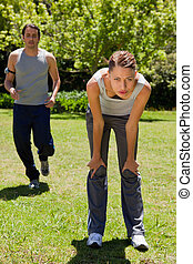 Woman bending over while a man is jogging in the background...