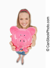 Fisheye view of a young woman tending a piggy-bank against...