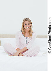 Woman sitting with folded legs on the bed - A smiling woman...