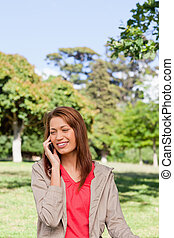 Woman happy while making a phone call in and area surrounded by trees