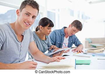 A side view shot of a group of studying students as one...