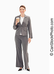 Smiling businesswoman holding cup of coffee - A smiling...
