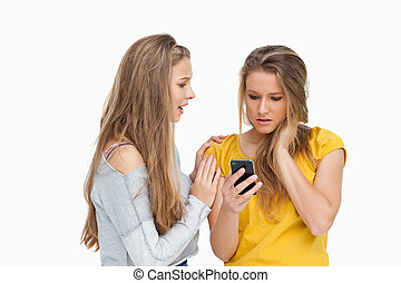 Upset young woman holding her cellphone consolded by her friend