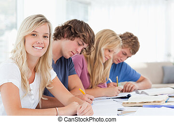 Students working as one girl smiles and looks at the camera