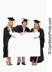 Three students in graduate robe holding and pointing a blank...
