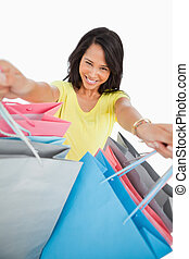 High-angle view of a young woman showing shopping bags...