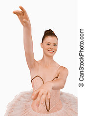 Smiling ballerina with her arms extended against a white...