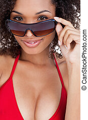 Attractive brunette woman looking over her sunglasses...