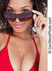 Attractive brunette woman looking over her sunglasses