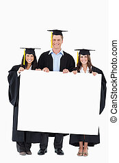 A full length shot of three graduates holding a blank poster...