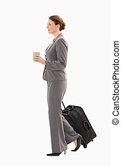 Businesswoman with suitcase holding coffee - A businesswoman...
