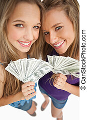 High-angle shot of two happy young beauty holding dollars...