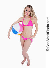 Smiling blonde teenager holding a beach ball under her arm