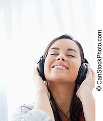 Close up shot of a smiling woman listening to her headphones