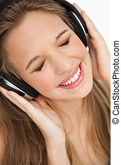 Close-up of a cute young blonde listening to music