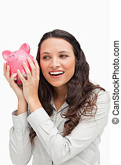 Brunette shaking a piggy bank against white background