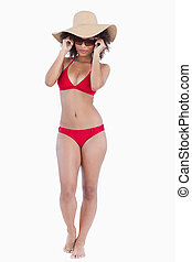 Attractive young woman in beachwear standing upright