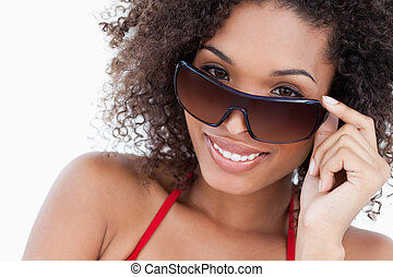 Smiling young brunette looking over her sunglasses against a...