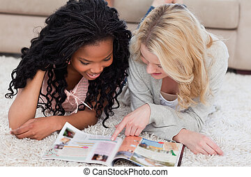 Two women lying on the floor with a magazine in front of...