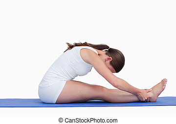 Young woman sitting on a yoga mat against a white background