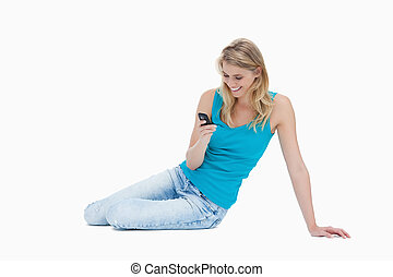 A smiling  woman sitting on the floor is holding her mobile phone against a white background
