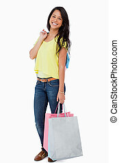 Happy Latin student with shopping bags against white...