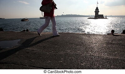 people walking seaside with maiden tower in istanbul