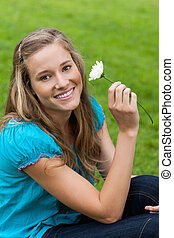 Young smiling woman holding a flower while sitting down -...