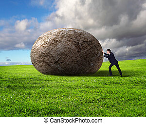 Businessman rolling a giant stone - Image of businessman...