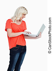 Woman standing upright while using the touchpad of her...