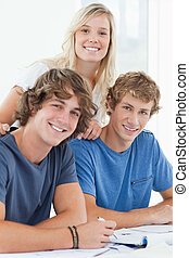 Three smiling students as they look at the camera