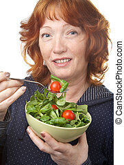 mature woman eating salad isolated