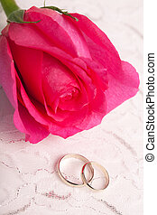 Gold wedding rings and pink rose
